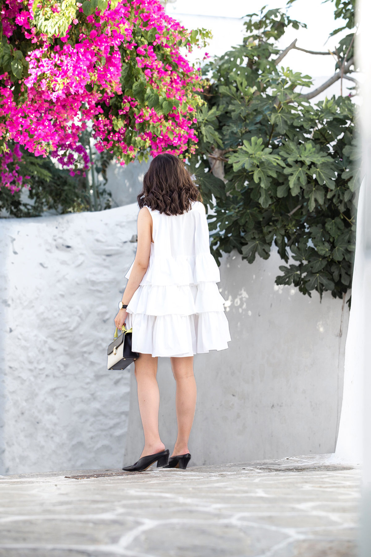 Stella Asteria, fashion & lifestyle blogger, wearing a little white frilled dress in Mykonos