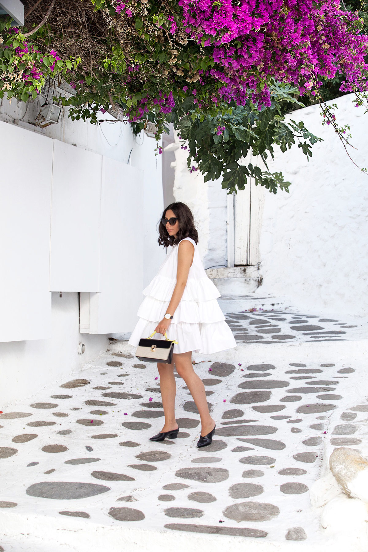 Stella Asteria, fashion & lifestyle blogger, wearing a little white frilled dress in Mykonos Greece