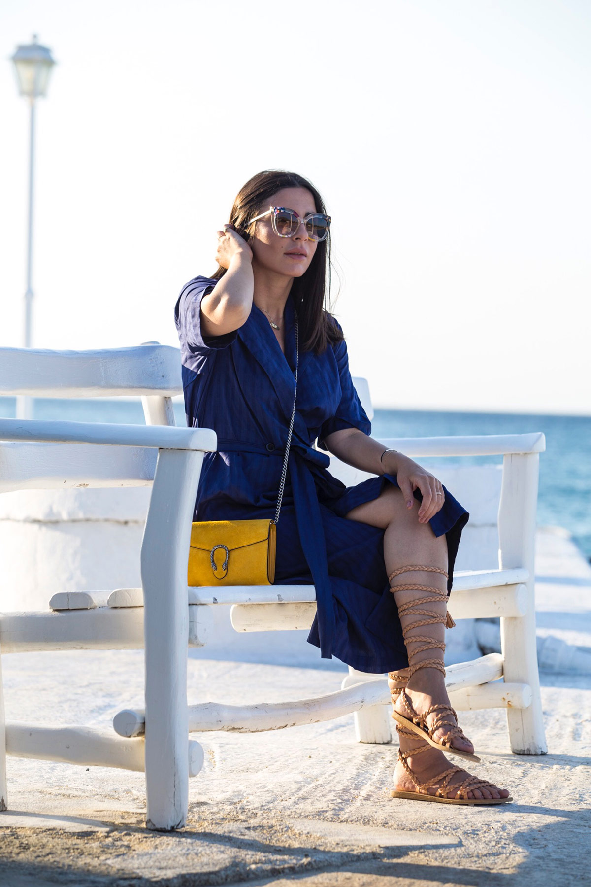 Stella Asteria wearing blue dress & yellow Gucci Dionysus bag, and Fendi sunglasses in Mykonos