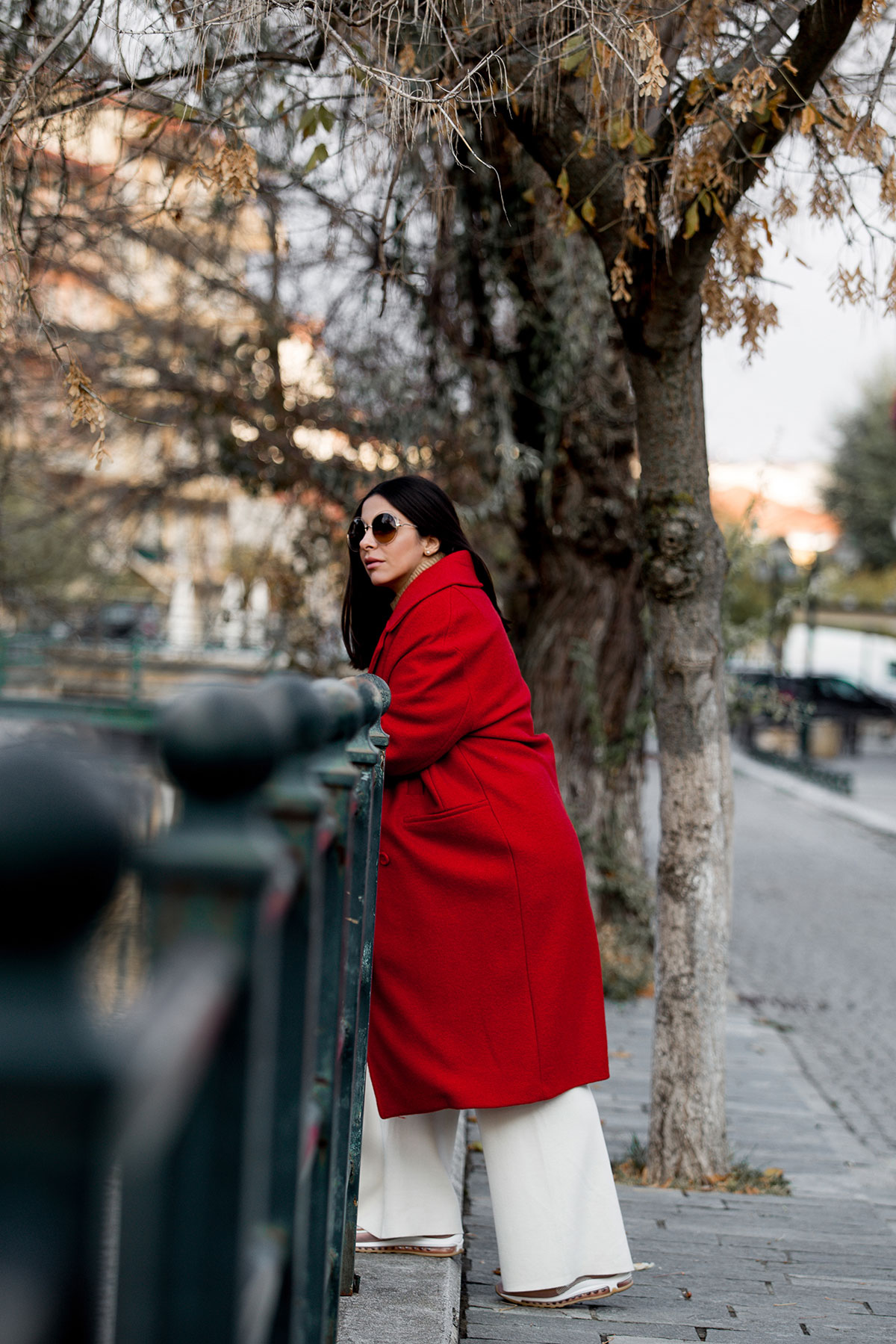 How To Wear A Red Coat - Stella Asteria wearing red coat with beige neutrals, pink Nike millennium sneakers, Louis Vuitton Palm Springs backpack and Chloe sunglasses