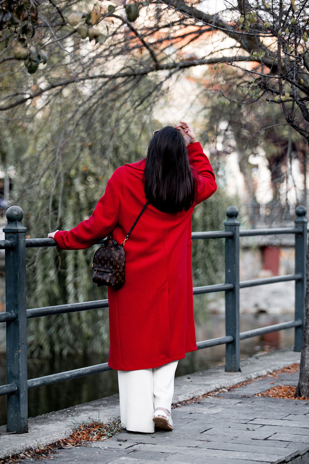 Red coat & Louis Vuitton Palm Springs backpack ass seen at Stella Asteria - Fashion & lifestyle blogger - travel look idea