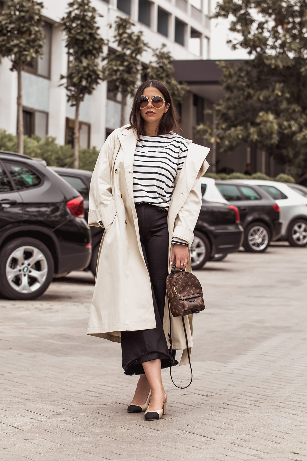 Stella Asteria wearing classic look with beige trench coat, breton top, Louis Vuitton Palm Springs backpack as a cross body, black denim culottes, Chanel slingbacks and Chloe Carlina sunglasses