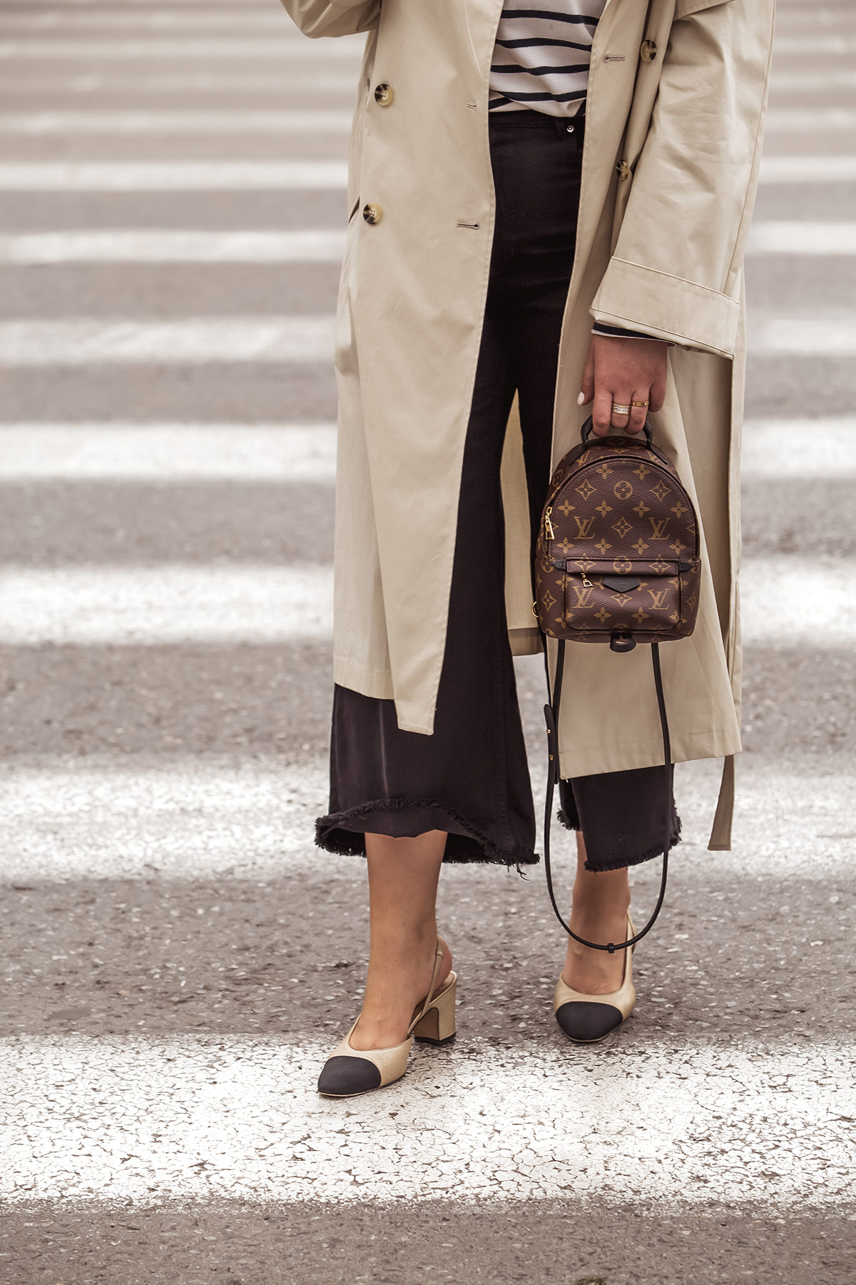 Louis Vuitton Palm Springs backpack, denim culottes, beige trench coat and Chanel classic slingbacks as seen at Stella Asteria