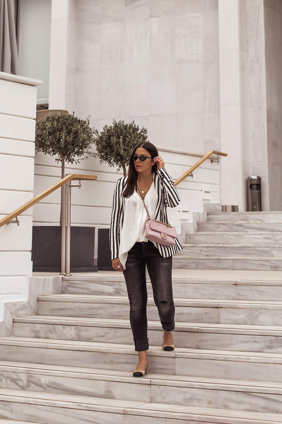 Stella Asteria showing how to wear a striped blazer for spring - striped blazer from H&M, dark grey jeans, Chanel slingbacks, white top and pink Chanel chevron bag, Le Specs cat-eye sunglasses