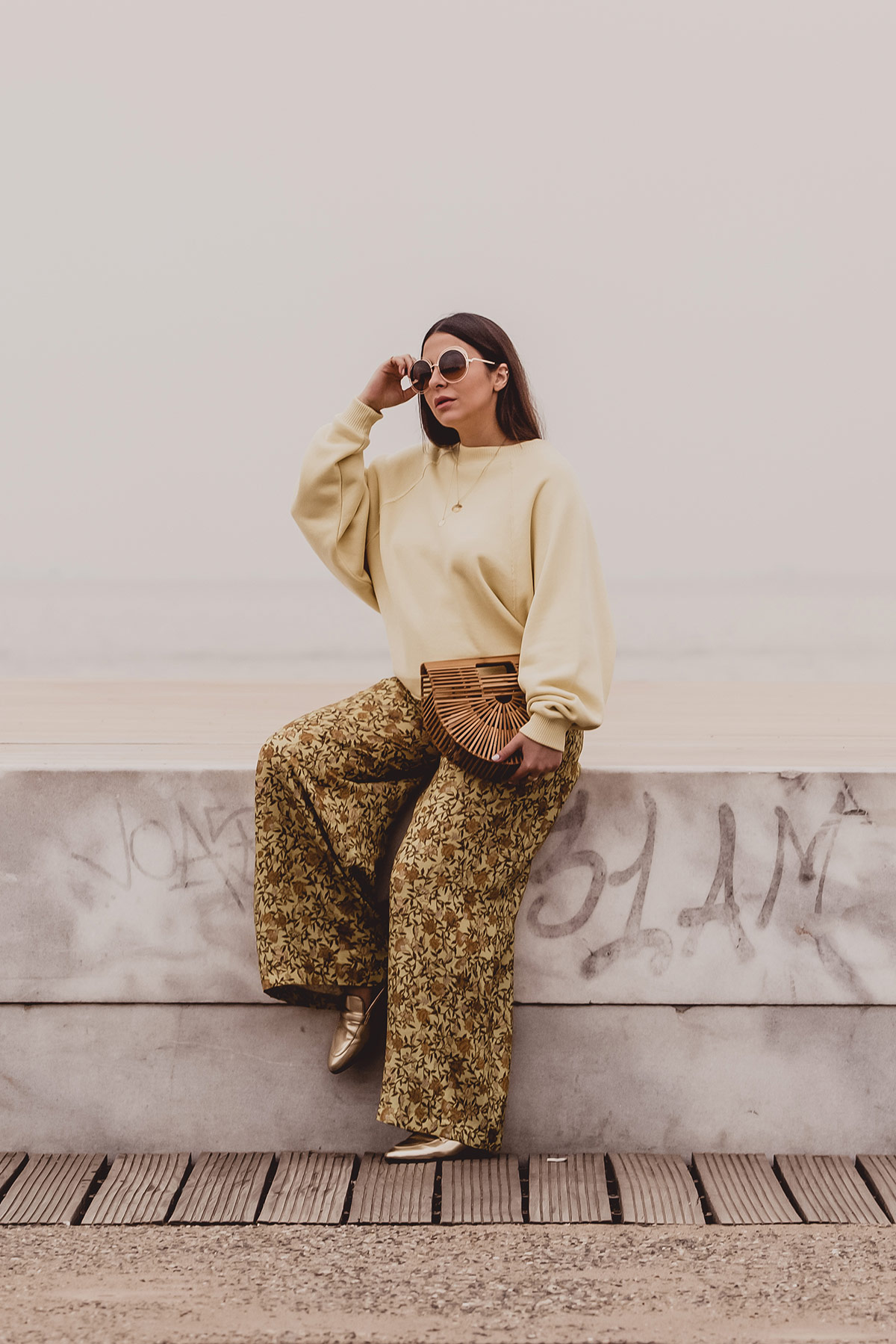 yellow trend Spring Summer 2018 - yellow outfit by Stella Asteria - Fashion & Style Blogger wearing yellow floral pants, yellow sweatshirt, Cult Gaia bag, and Chloé sunglasses