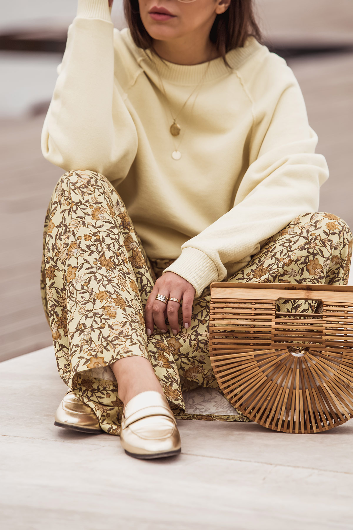 Cult Gaia bag as seen at Stella Asteria - Fashion & Lifestyle Blogger wearing a yellow outfit with golden flat mules and the iconic Cult Gaia arch bag.