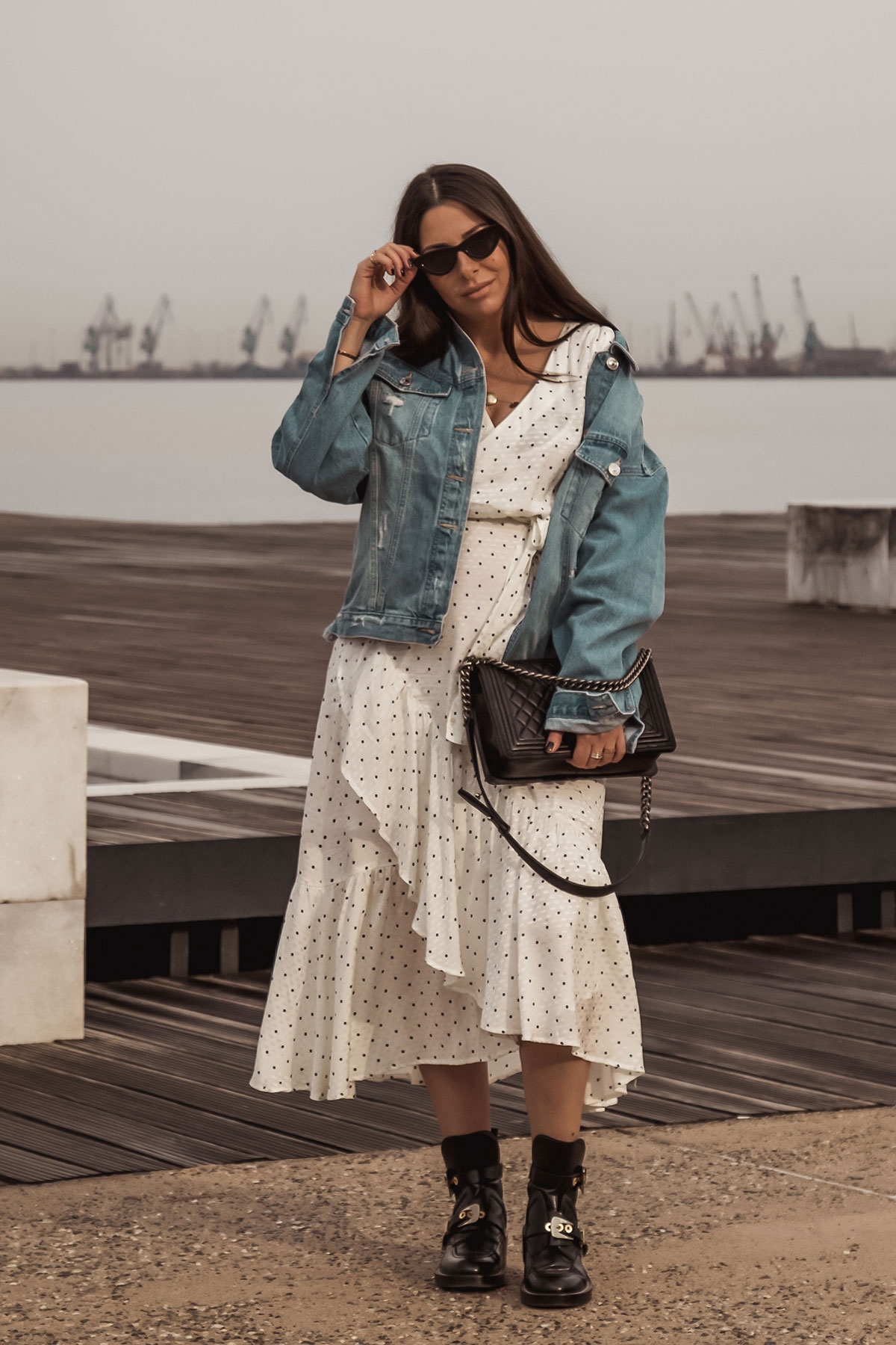 Stella Asteria wearing white polka dot dress with edgy black boots, denim jacket & Chanel boy bag - Spring/Summer 2018 fashion style inspiration