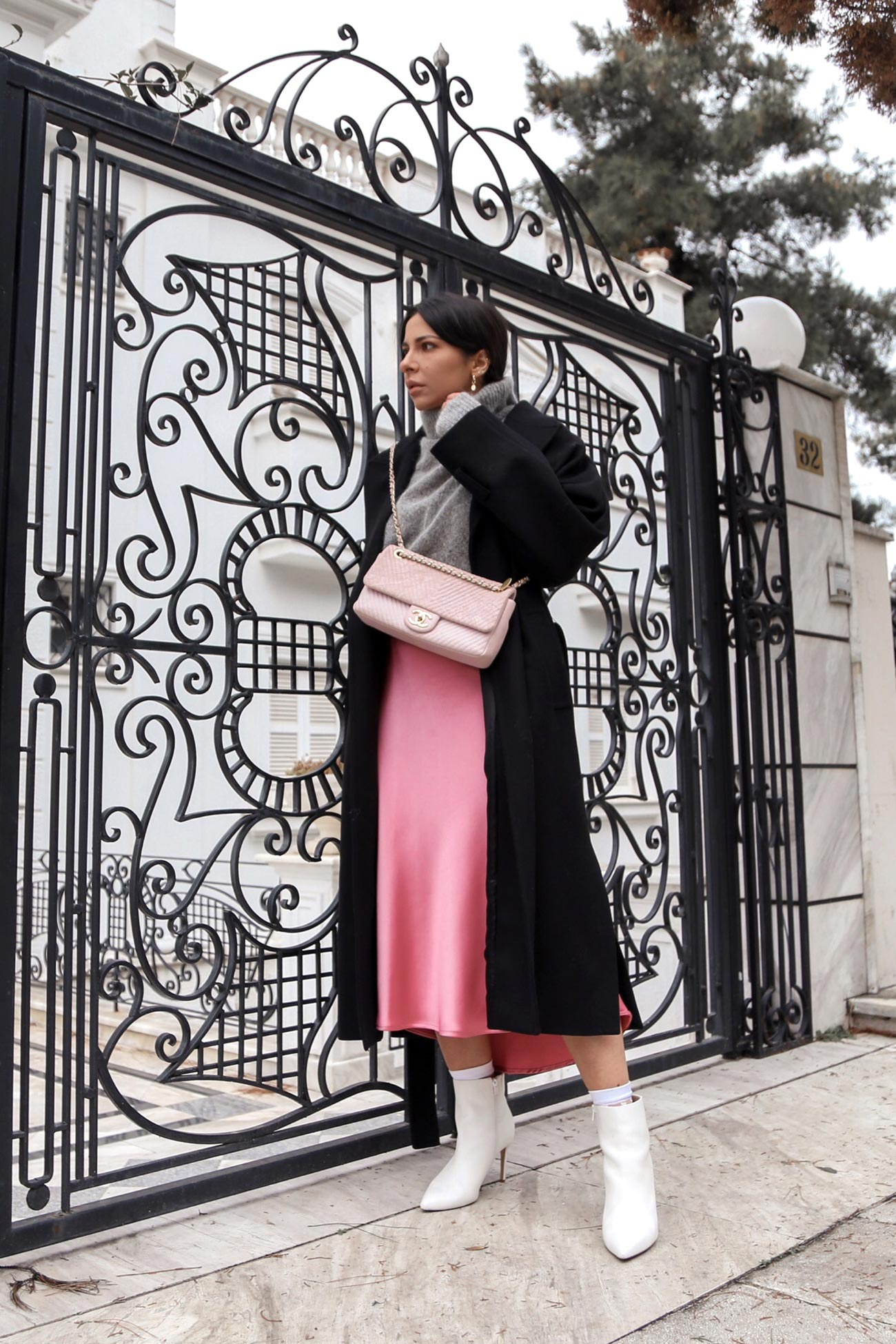 Stella Asteria wearing pink skirt paired with pink Chanel bag and white boots