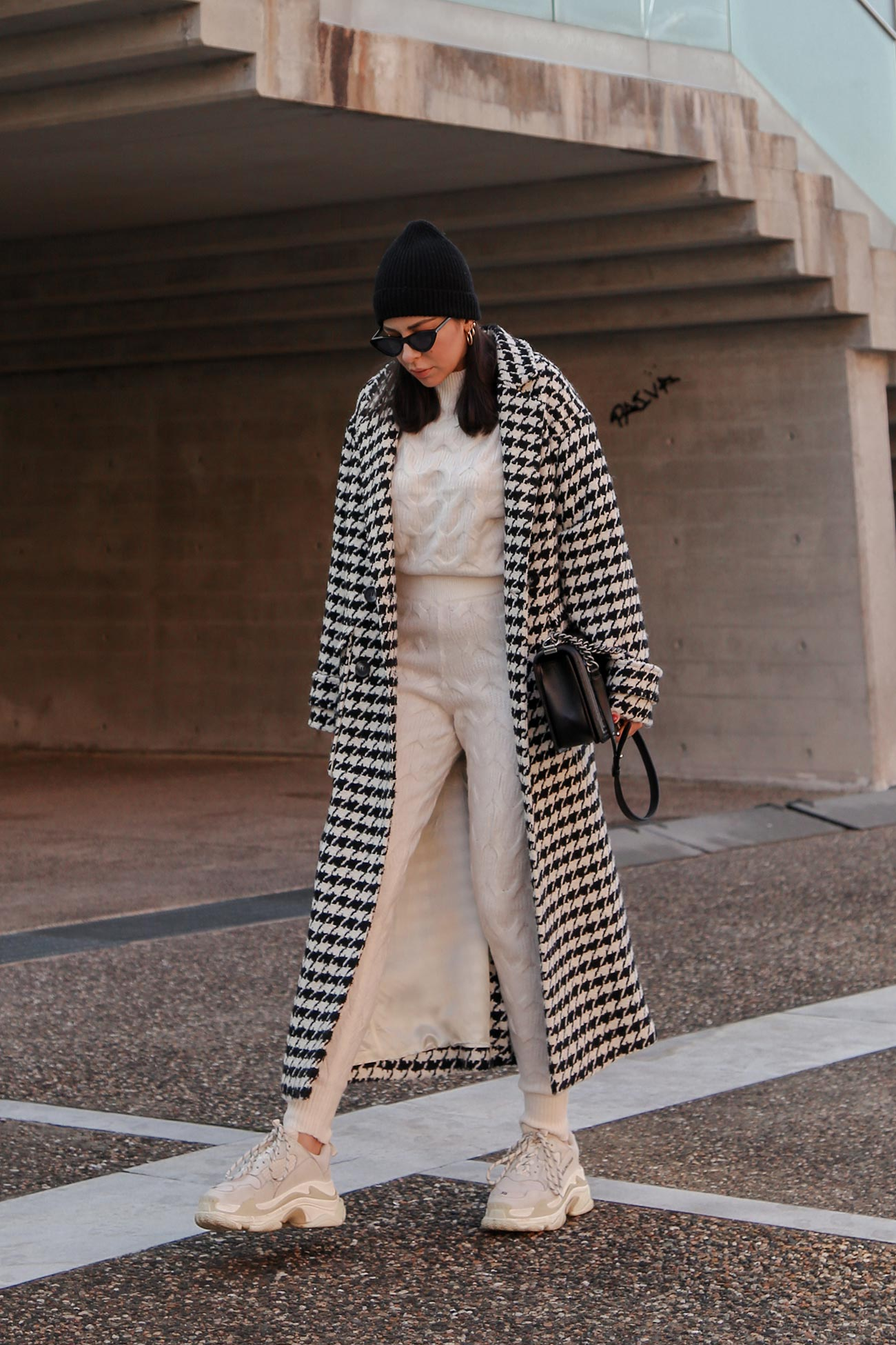 Stella Asteria wearing knit co-ord with white Balenciaga Triple S and longline black and white houndstooth coat