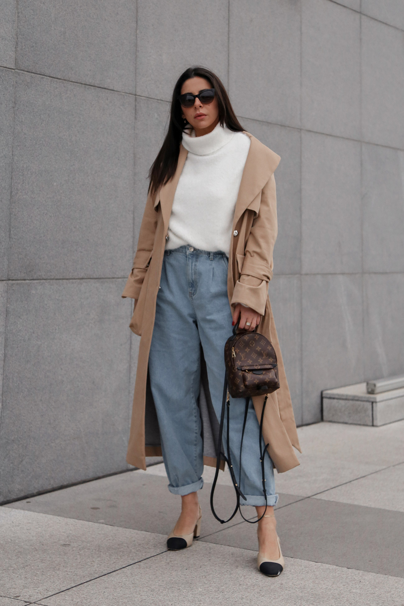 Stella Asteria wearing beige trench coat, jeans, white sweater, Chanel slingback and Louis Vuitton backpack