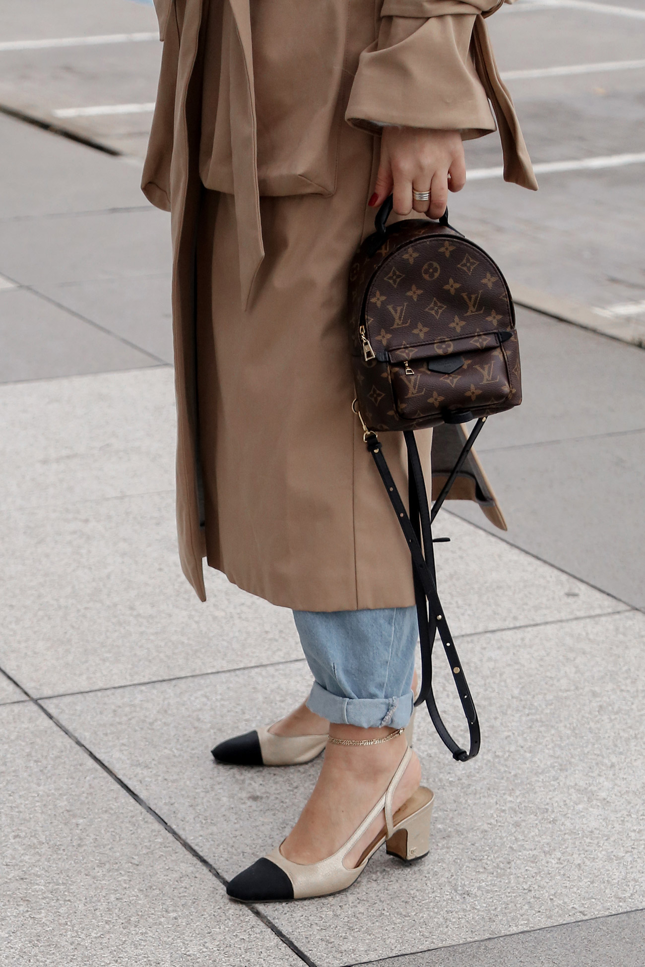Outfit details from Stella Asteria wearing beige trench coat with Chanel slingback and Louis Vuitton backpack