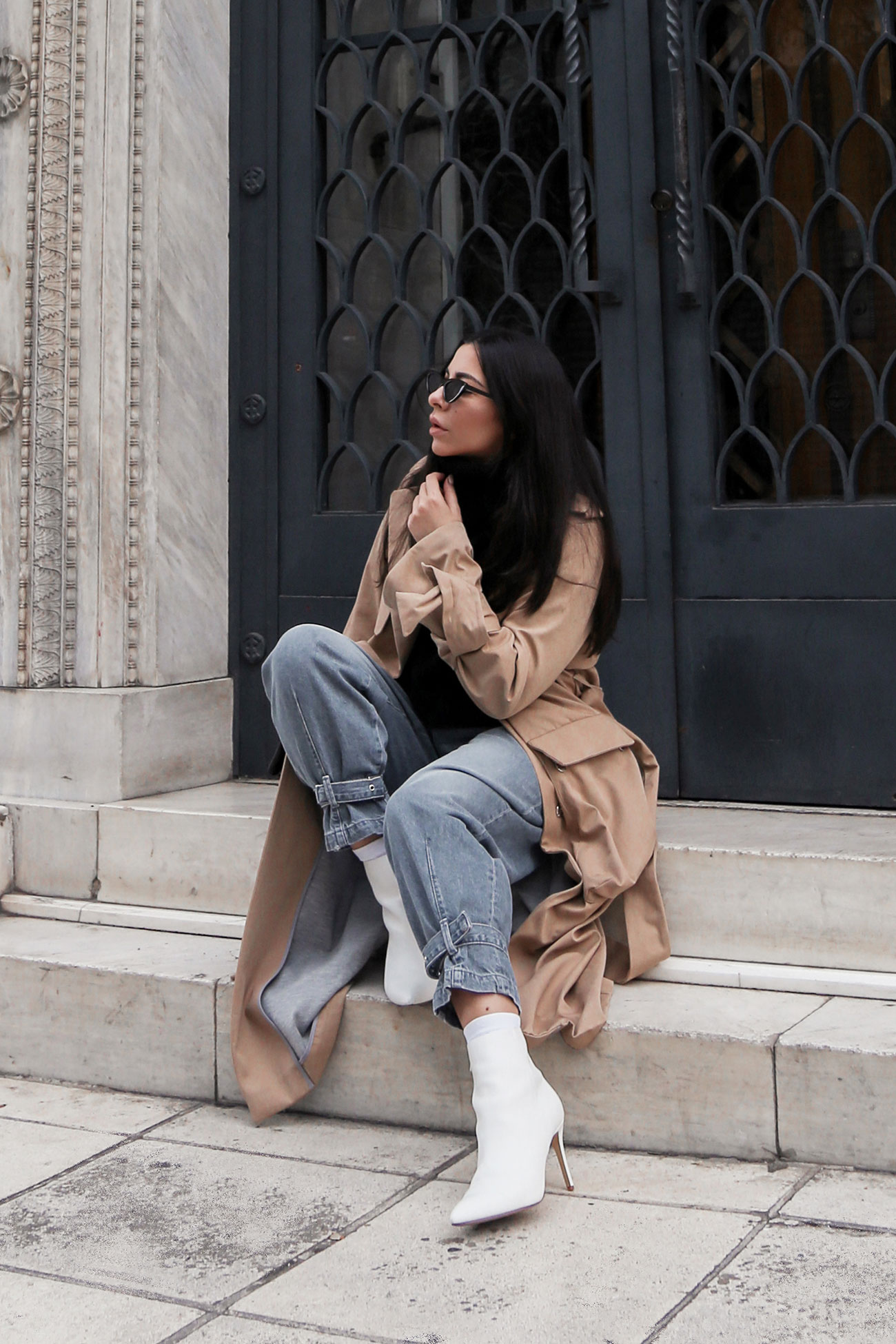 Stella Asteria wearing one of her beige trench coats with jeans and white ankle boots