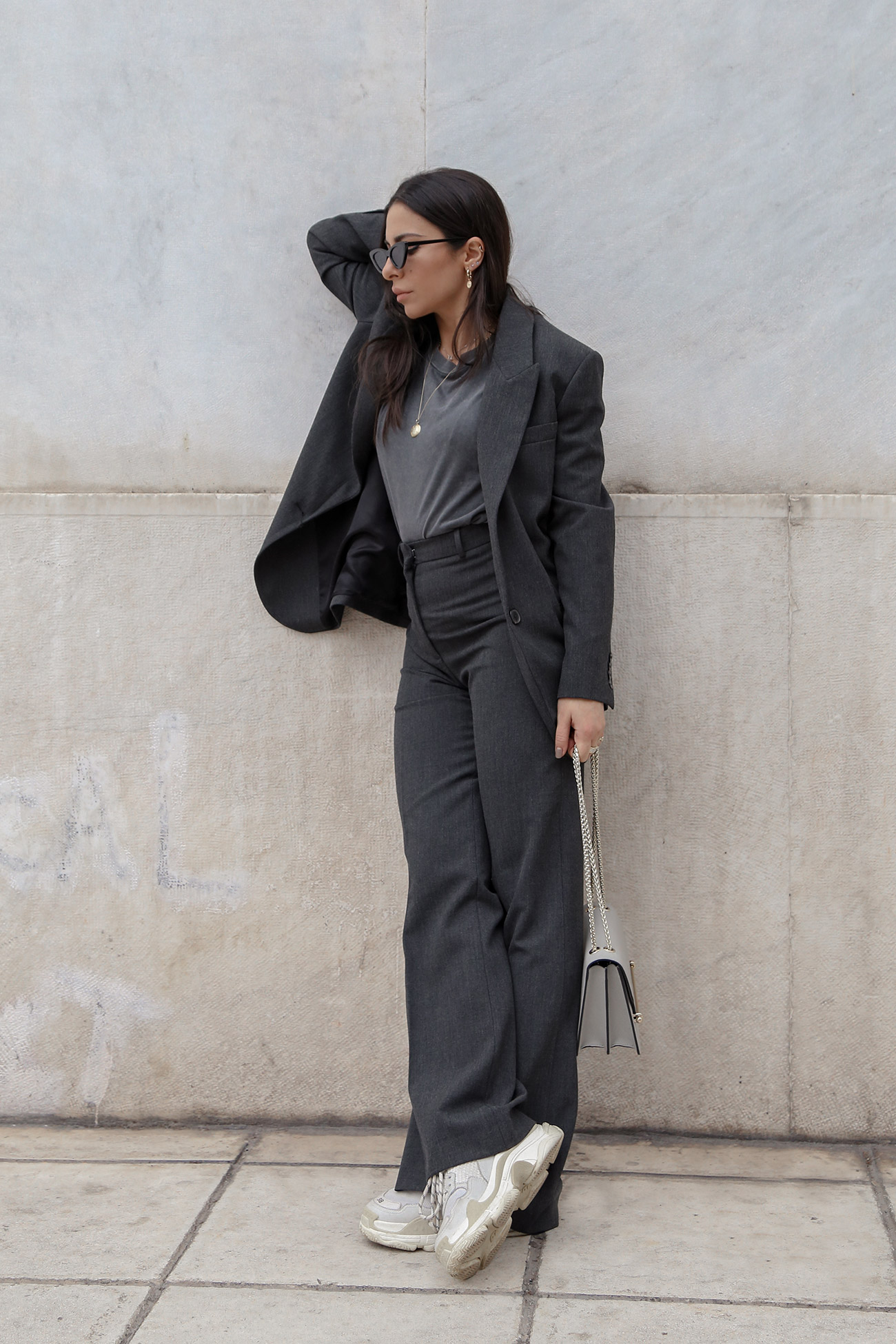 Stella Asteria wearing a grey women's suit casually with Balenciaga Triple S sneakers & Strathberry bag