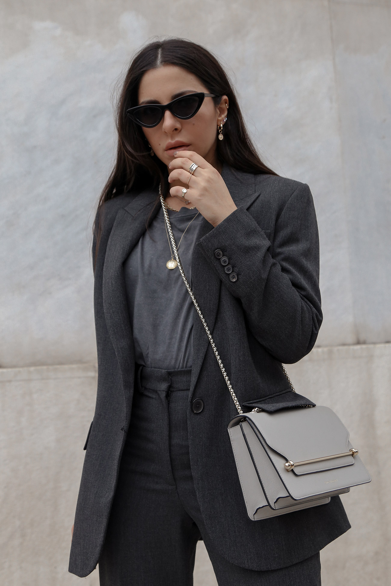 Stella Asteria wearing grey suit with grey Strathberry bag