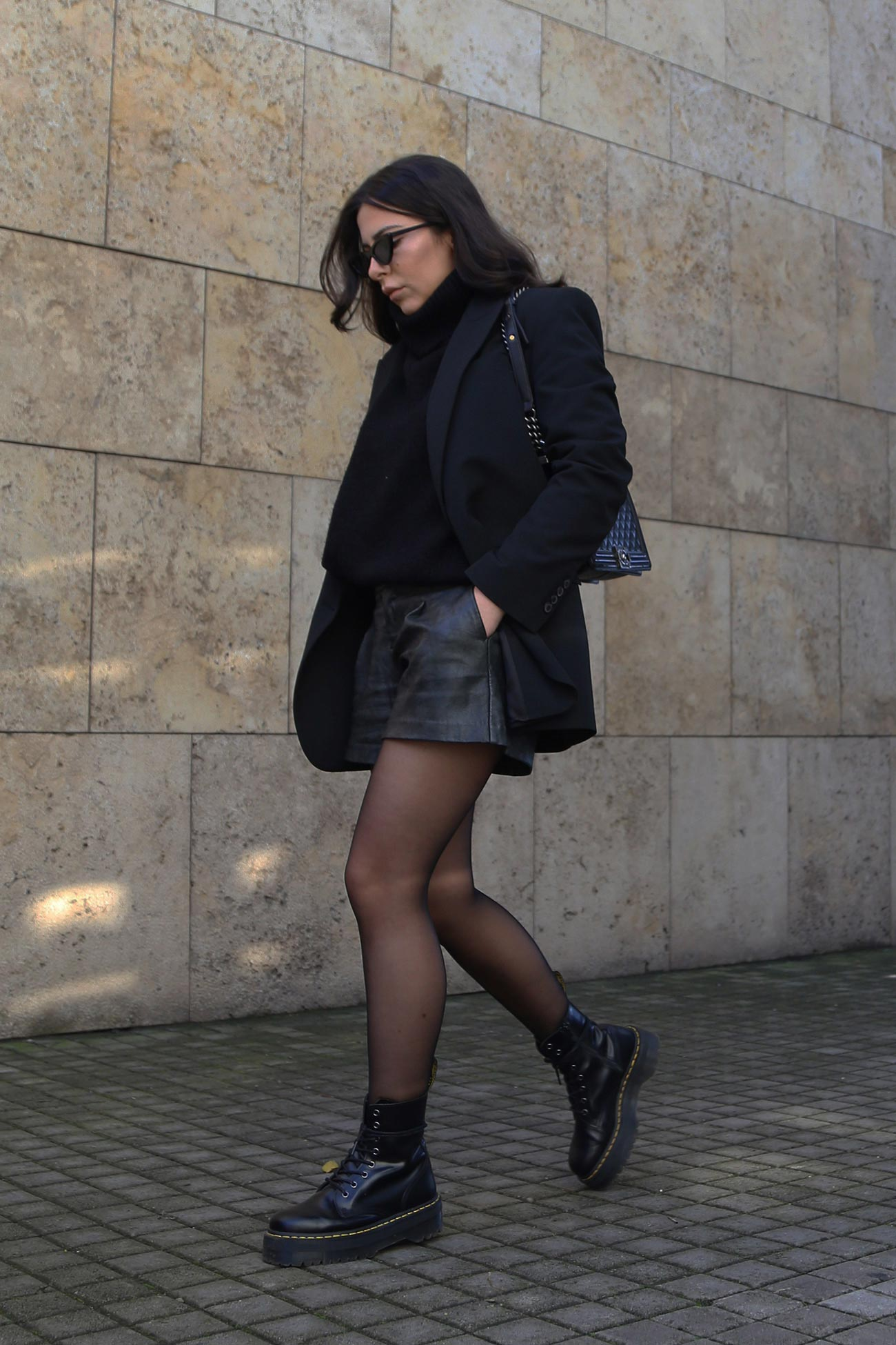 Stella Asteria wearing leather shorts, black blazer with sweater, Dr Martens boots and Chanel boy bag