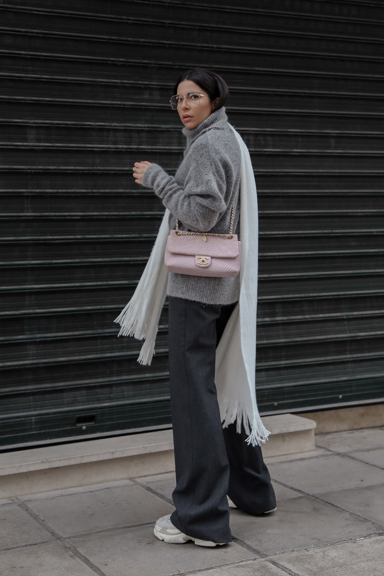 Stella Asteria wearing suit pants wth sweater, sneakers and Chanel bag
