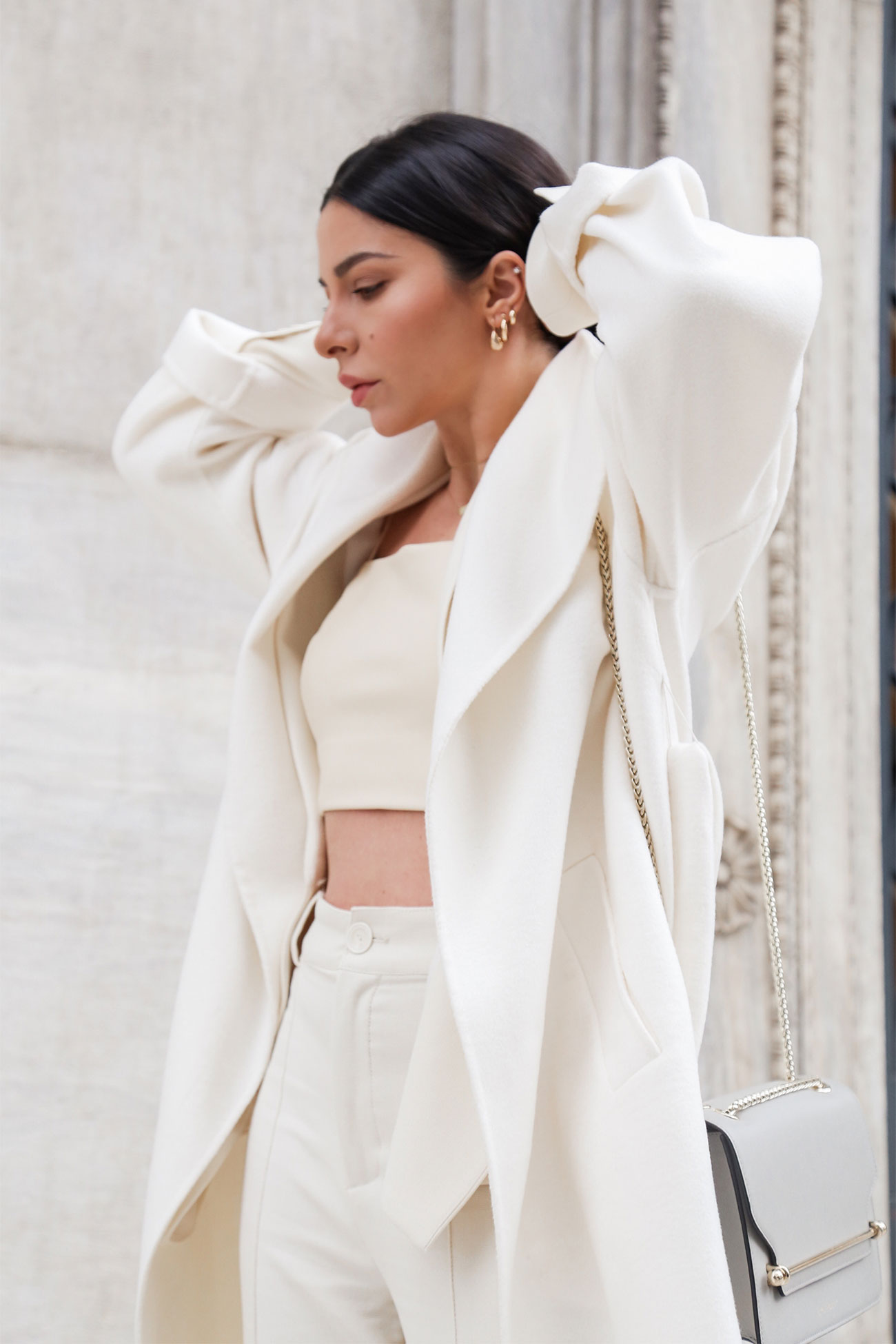 Stella Asteria wearing a total white look with soft wool coat, white pantsuit, faux leather crop top and Starthberry east west bag. How to wear a head-to-toe white outfit