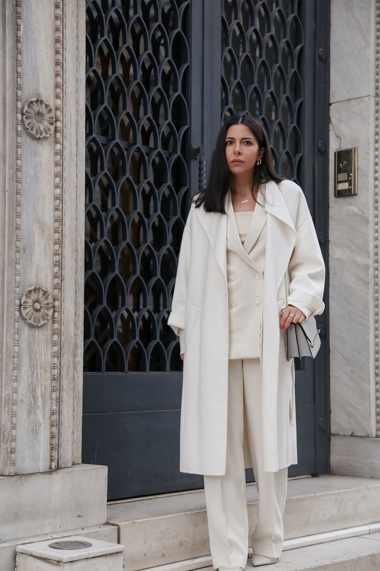 Total white look by Stella Asteria, wearing a white pantsuit with wool coat, faux leather top, high heels in white and Strathberry bag in grey