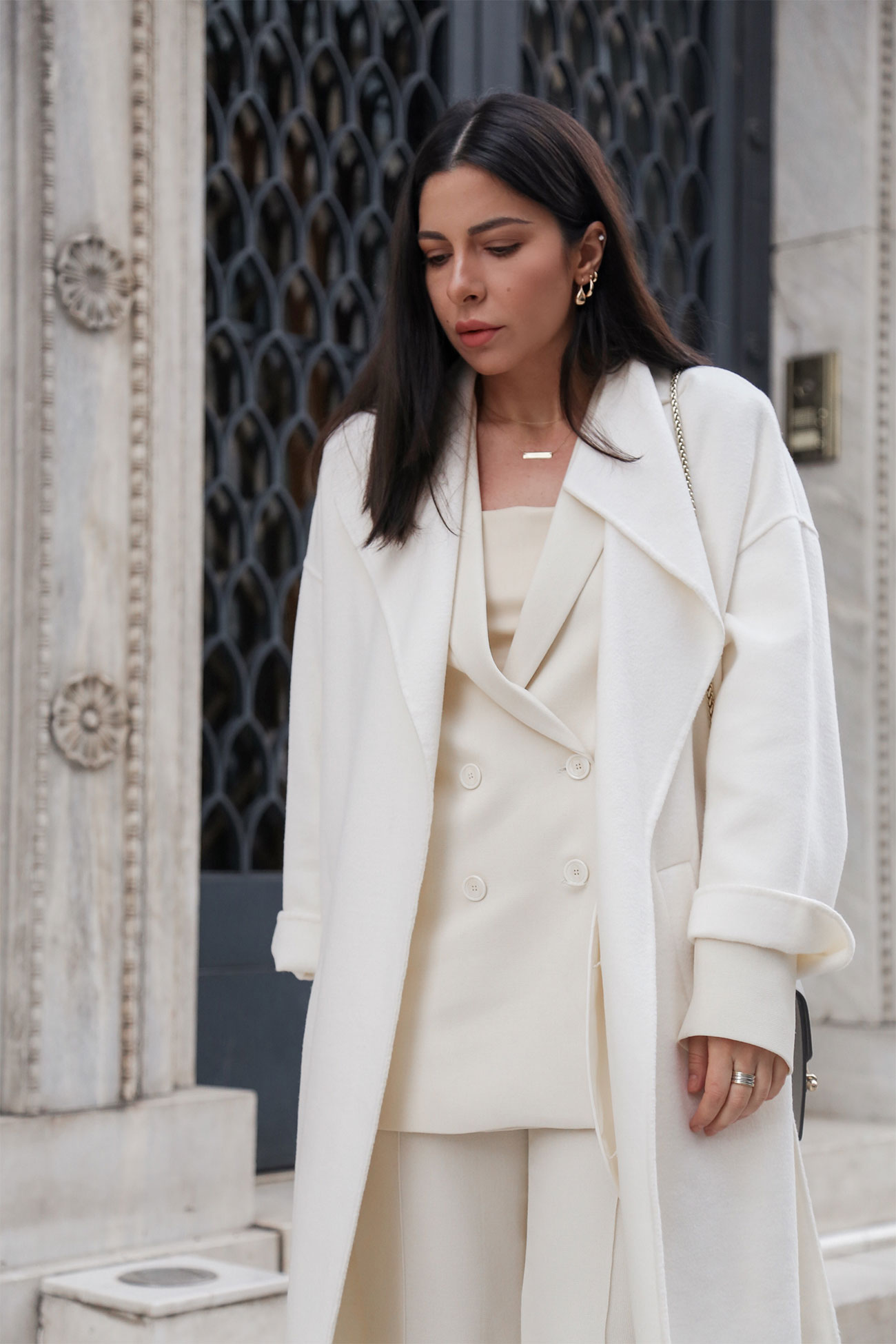A perfectly layered total white look by Stella Asteria - wearing head-to-toe white outfit with white pantsuit, white wool coat and a faux leather top in the same color